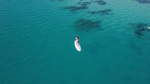 Aerial view of young girl stand up paddling on vacation. Tracking shot of a Footage