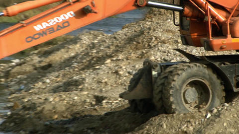 Excavator with bucket which carries out the iron gravel from the riverbed and st Footage