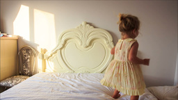 Little Girl Jumps up and down White Bed to Pillows on Floor Footage