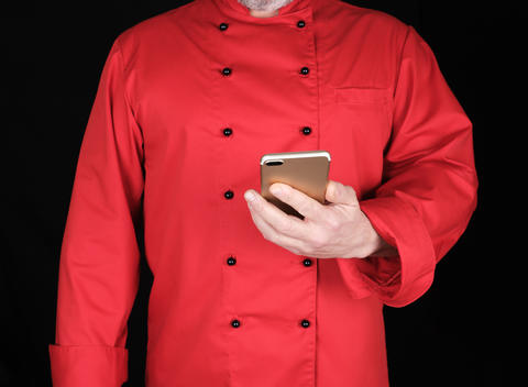 chef in red uniform holds in his hand a smartphone フォト