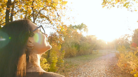 Beautiful brunette walking along autumn park and looking around. Bright sun rays Footage