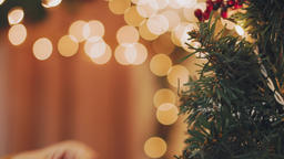 Hand woman decorating on Christmas tree with Christmas glow lights Footage
