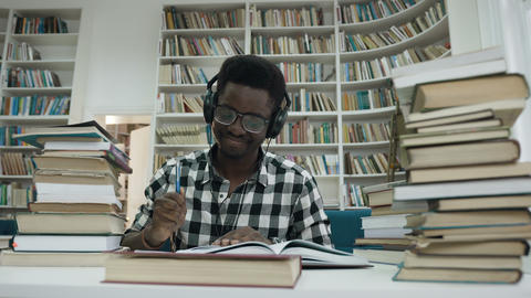 African male student with headache throwing pen after he finish writing lecture Live Action