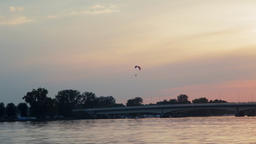 Paraglider is Paragliding in the City with Golden Sunset Sky and Lake Background ビデオ