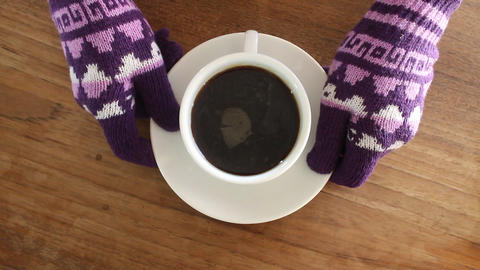 Hand gloved hold a cup of coffee Live Action