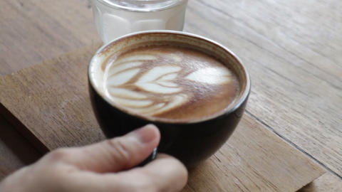 Woman enjoying hot coffee latte in the local shop Live Action