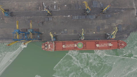 Aerial 4k UHD footage Cargo freight ship with working crane bridge in shipyard Live Action