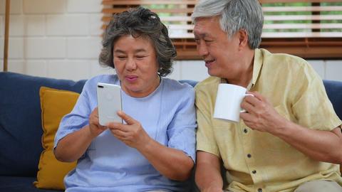 Asian senior couple having video chat using smartphone. Sharing social media Live Action
