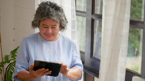 Portrait asian senior woman using tablet searching online shopping. Sharing Footage