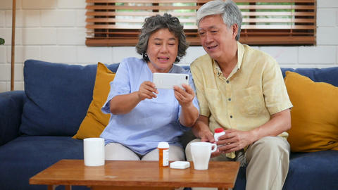 Asian senior couple having medical consultation video chat on mobile. Sharing Footage