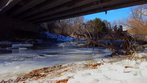 Frozen River Under a Bridge in Winter. Water Flowing in Ice River Under Road Live Action
