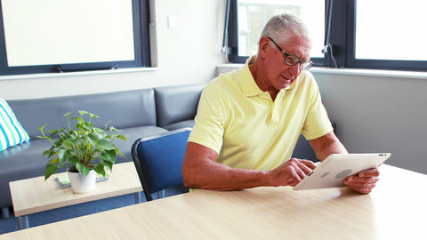 Retired man using tablet computer Live Action