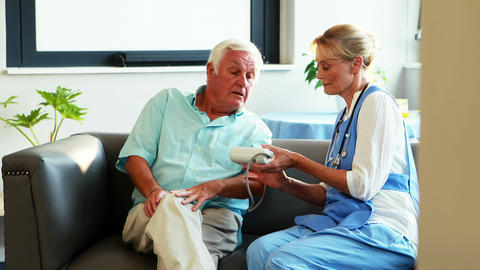 A nurse measuring blood pressure of a senior man Live Action