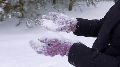 Woman shakes off snow from winter knitted gloves, winter clothes, snow in slow Live Action