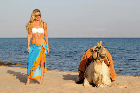 Blonde girl in sunglasses and white bikini and blue pareo standing near camel. Photo