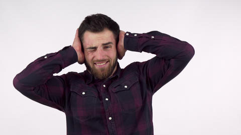 Bearded man covering his ears from a loud noise Live Action