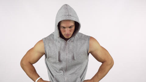 Strong muscular man wearing hoodie, looking fiercely to the camera Live Action