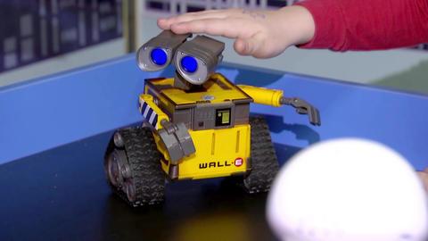 Boy stroking the hand of a small robot toy, the interaction of the robot Acción en vivo