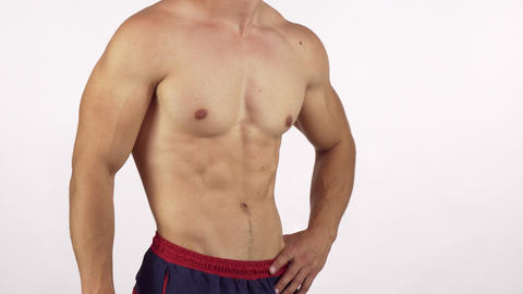 Muscular man with perfect abs flexing his muscles isolated Footage