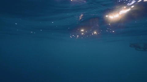 Underwater view golden sun rays shining through blue sea water. Bright sunshine Footage