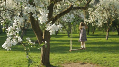 Unrecognizable little girl enjoying the free time, swaying on a wooden swing GIF