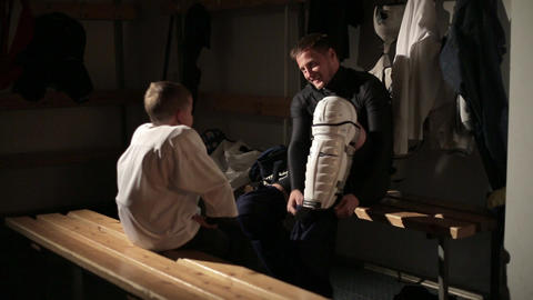 Dad and son hockey player dress up in the locker room 12 of 42 Live Action