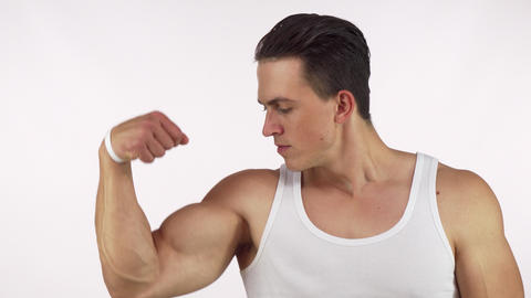 Muscular young man flexing his bicep looking to the camera fiercely Live Action