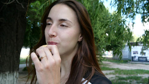 A girl shows a cookie and eats it in slow motion GIF