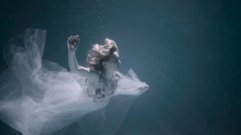 Young women in a white dress swimming under the water Footage