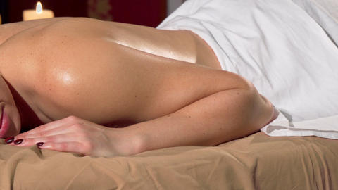 Woman resting on massage table at the spa, candles burning on background Footage