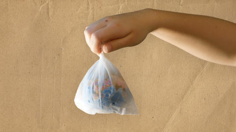 a teenage girl holds a plastic bag in her hand that contains a mini globe Live Action