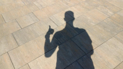 The shadow of a man shows gesture cool Live Action