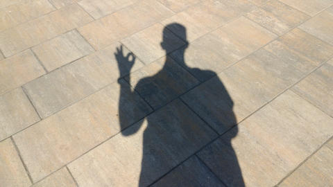 The shadow of a man shows gesture ok Live Action