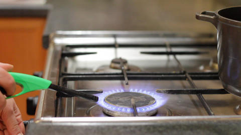 woman lights gas and puts pan on gas cooker Stock Video Footage