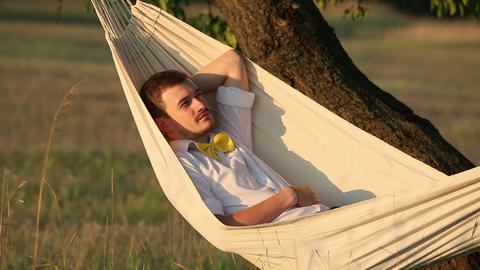 Young man swinging on hammock at sunset Stock Video Footage