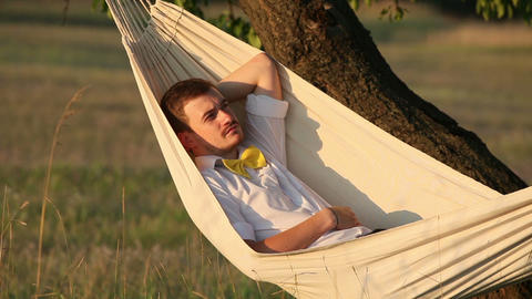 Young man swinging on hammock at sunset Footage