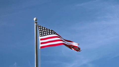 USA flag flying on the wind on blue sky background Footage