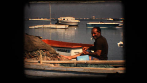 Vintage 8mm. Fisherman working on his boat Stock Video Footage
