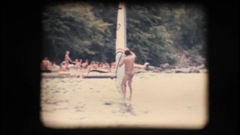 Vintage 8mm. Windsurfer preparing his sail Footage