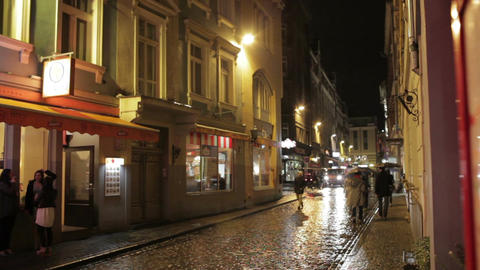 People walking along street bars and restaurants in the evening in the old city of Riga after the ra Footage