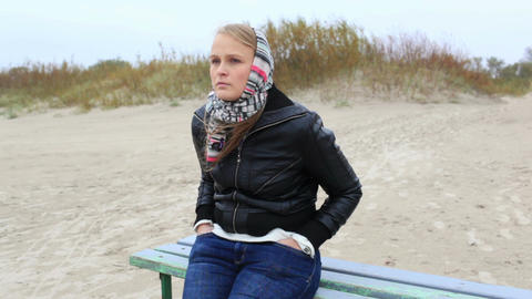 Young melancholy girl is sitting on a bench near the sea Stock Video Footage