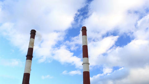 Two factory chimneys and blue sky. Time lapse Footage