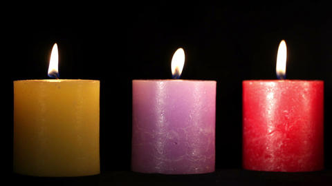Yellow purple and red candles isolated on black. Holiday background with copyspace for text Footage