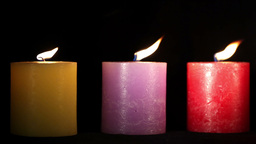 Yellow purple and red candles isolated on black. Holiday... Stock Video Footage