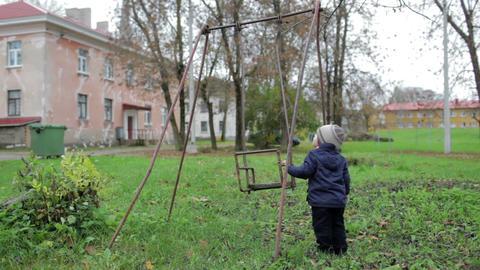 The little boy is swinging an old swing Footage
