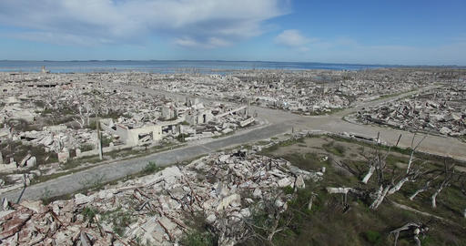 Aerial scene of destroyed town. Scene starts at pedestrian view and ends with pa Footage