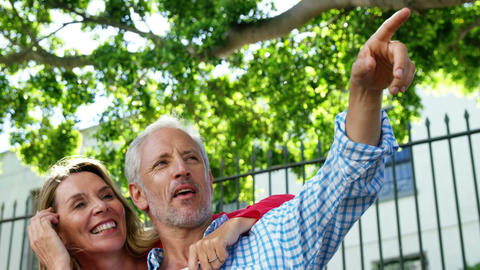 Portrait of mature couple is embracing and pointing Live Action