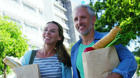 Mature couple is walking on the street with groceries Live Action