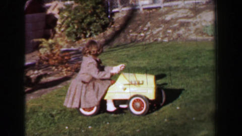 1957: Boy girl riding vintage antique toy pedal car in front lawn Footage