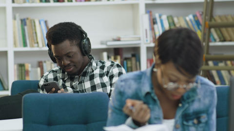 Attractive african female student reading book in the modern library while Live Action